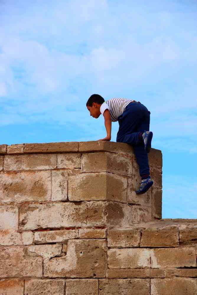 Maroc - Enfant qui grimpe sur les remparts dans le port d'Essaouira