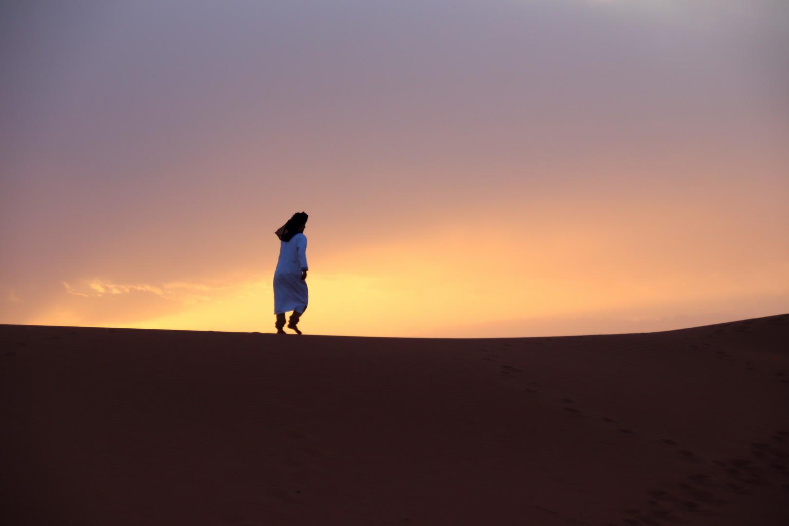 Maroc - Homme bleu sur la crête d'une dune de l'erg Chegaga pendant le coucher de soleil