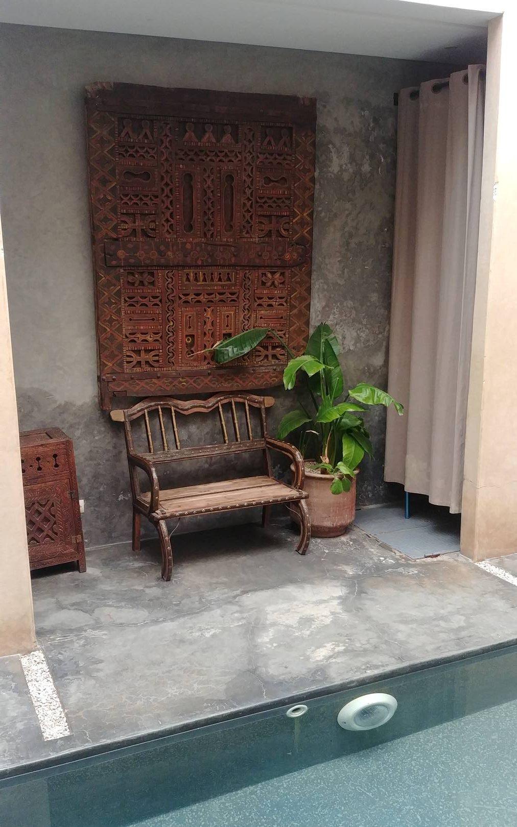 Maroc - Petit banc en bois devant la piscine du riad à Marrakech