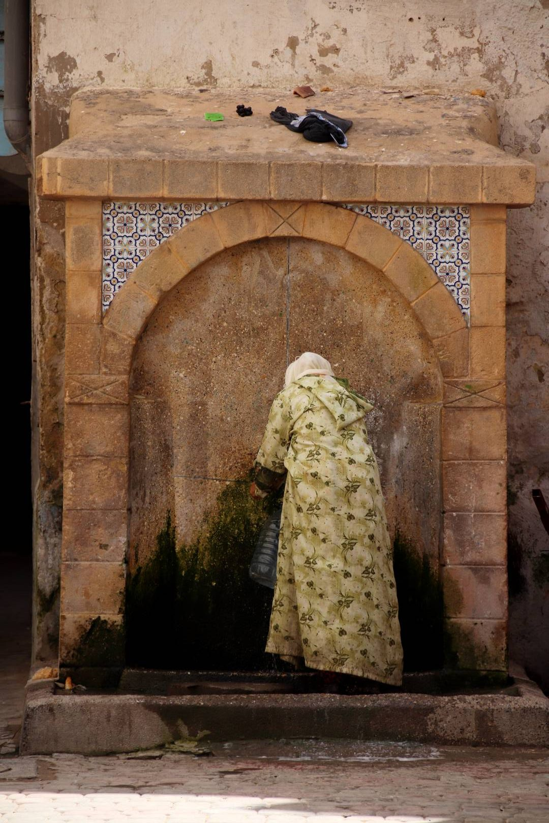Maroc - Femme à la fontaine dans la médina à Essaouira